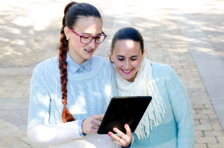 Two women using a tablet while Smiling photo