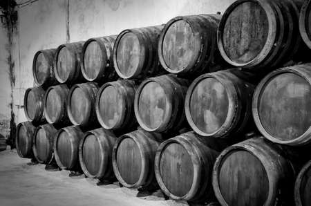 Whiskey or wine barrels in winery in black and white photo