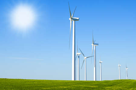 Windmills to generate wind power with blue sky and green meadow  photo