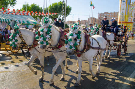 Seville, Spain, 8 may, 2014: People mounted on a carriage horse in fair Seville.