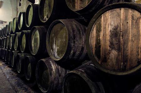 Wijn vaten gestapeld in de oude wijnmakerij Stockfoto