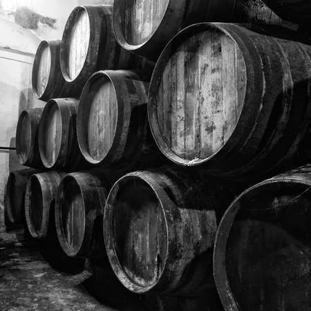 Wine barrels stacked in winery old, in black and white photo
