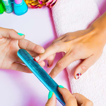 nailcare: Woman getting a manicure and nail painting in the foreground