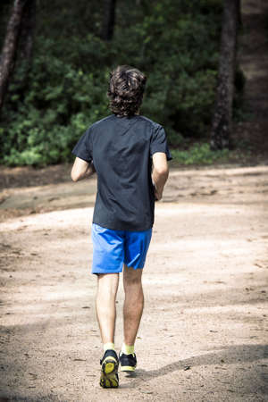 man field: Man running in the park, seen from behind