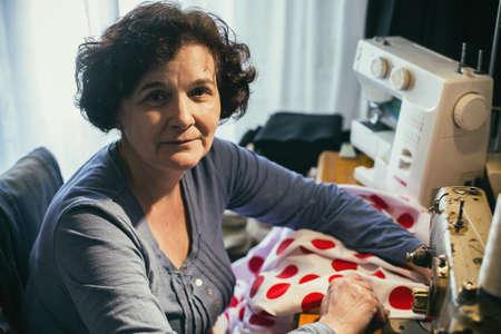 maquinas de coser: Mujer de costura de mediana edad Foto de archivo