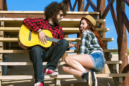 serenade: Young couple playing guitar Stock Photo