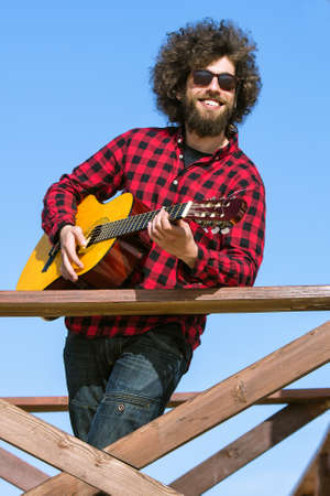 afro hair: Guitarist with plaid shirt and afro hair