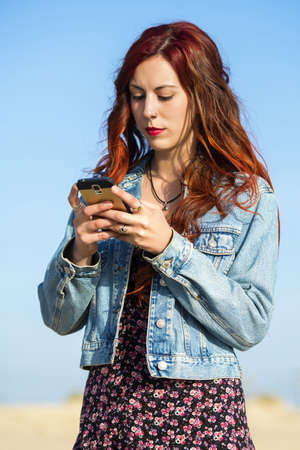 sober: Young redhead woman with smartphone Stock Photo