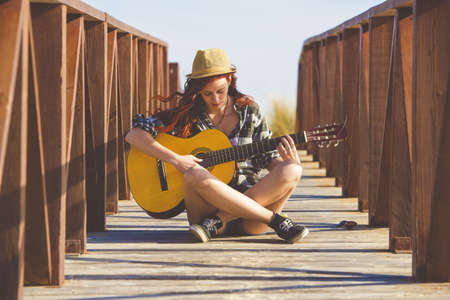 girl playing guitar: Woman playing guitar on the beach