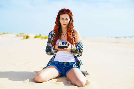 instant camera: Beautiful young woman with instant camera in the beach Stock Photo