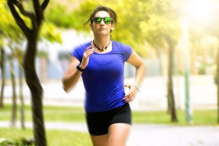 Woman running in the park with sunglasses Banque d'images