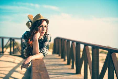 twentysomething: Young woman lying on the railing of beach Stock Photo