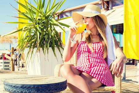 Young woman drinking a orange soda at a beach bar