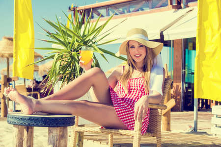 Young woman drinking a cocktail at a beach bar