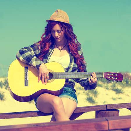 pastel colours: Mujer joven que toca la guitarra en tonos pastel Foto de archivo