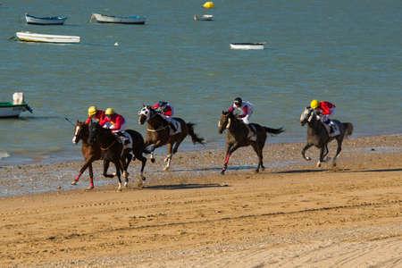 jockey's: SANLUCAR DE BARRAMEDA (CADIZ), SPAIN - AUGUST 22: Jockeys race along the beach during the traditional beach race of Sanlucar de Barrameda near Cadiz On aug 22, 2015 in Sanlucar de Barrameda (Cadiz). Editorial