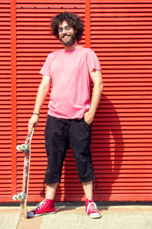 average guy: Man with skateboard on red background