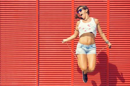 jumping: Cuerda de salto de la mujer sobre fondo rojo