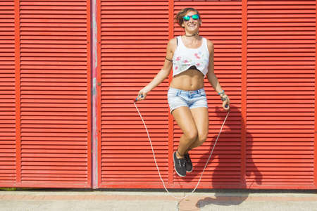 woman rope: Woman jumping rope on red background