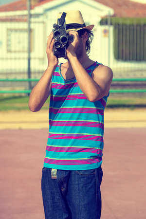 cinematographer: Young man with old film camera in patel colors