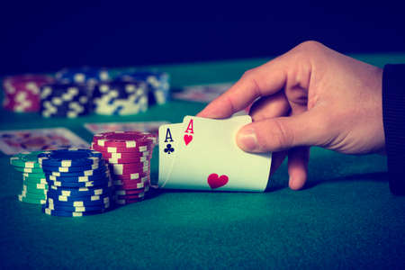 double the chances: Closeup of poker player with two aces in pastel colors Stock Photo