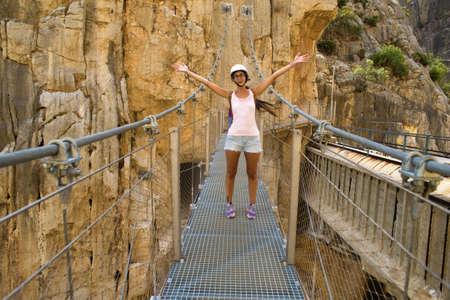 nature photo: Woman in the middle of a suspension bridge in the Caminito del Rey, Malaga, Spain.