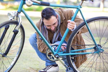 cadena rota: Hombre que controla la cadena de una bicicleta antigua
