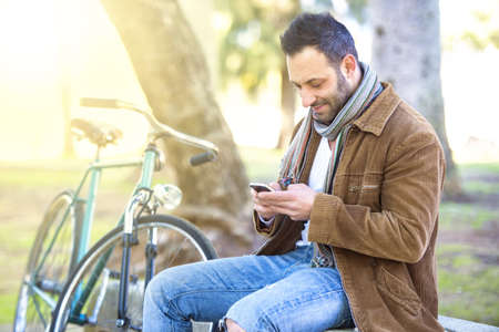 Man with mobile phone sitting on a bench in the park