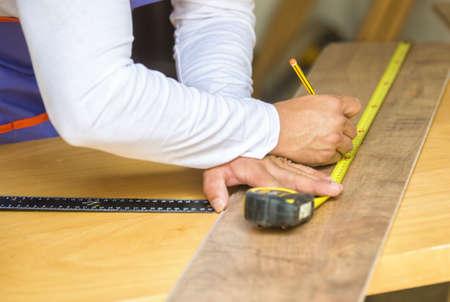 metro medir: Carpenter manos en el primer plano con la medición de metros
