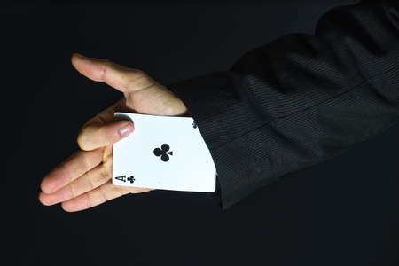 Man with ace up his sleeve on black background 免版税图像