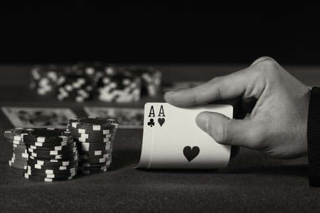 double the chances: Closeup of poker player with two aces in black and white Stock Photo