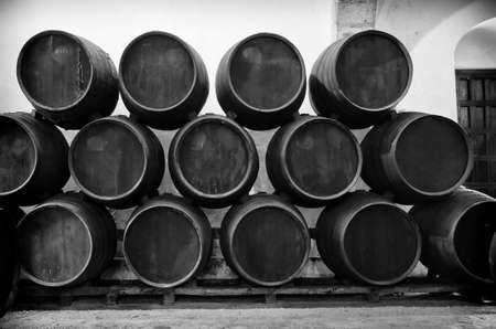 wooden barrel: Barrels stacked in the winery in black and white