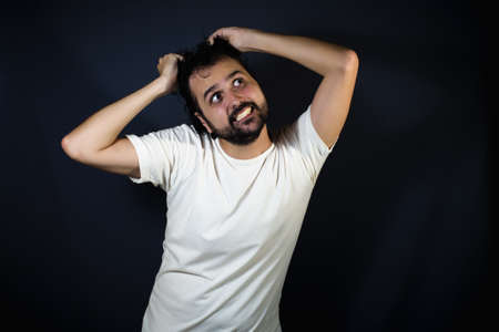 work addicted: Young man screaming and pulling their hair on black background