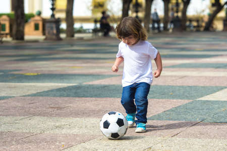 blonde boy: Child playing football on a concrete surface
