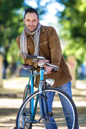 corduroy: Man with old bike and corduroy jacket in the park Stock Photo