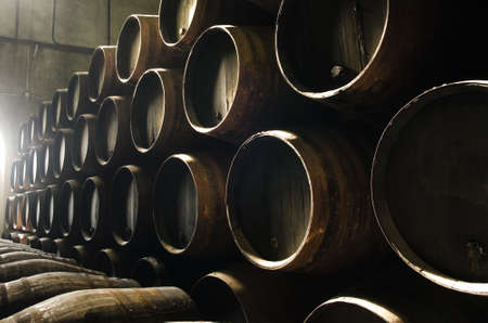 vintage timber: Barrels for whiskey or wine stacked in the cellar Stock Photo