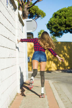 booty shorts: Back view of young woman in shorts on roller skates. Unrecognizable