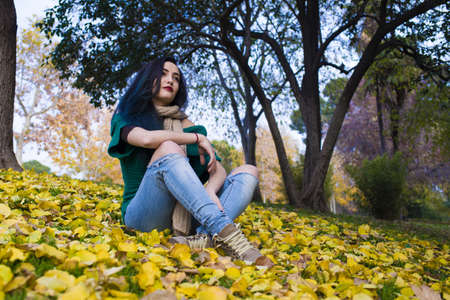 having fun in winter time: Portrait of young woman with blue hair sitting in park. Autumn