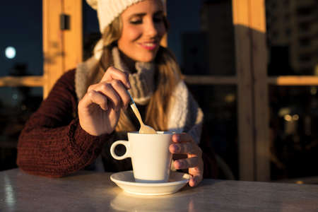 to get warm: Close-up cup of coffee with woman in background