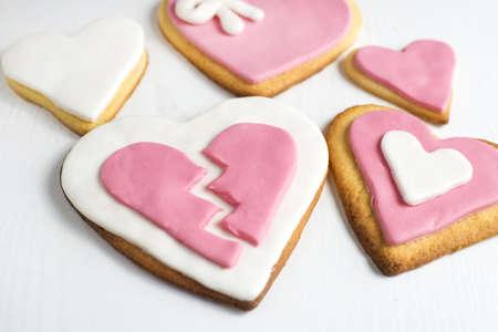 corazon roto: galletas hechas a mano con forma de coraz�n en madera blanca.