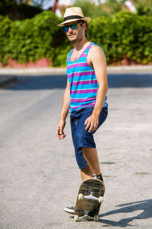 tank top: Man with skateboard wearing tank top and shorts