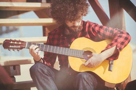 plaid shirt: Man Guitarist with plaid shirt and afro hair Stock Photo