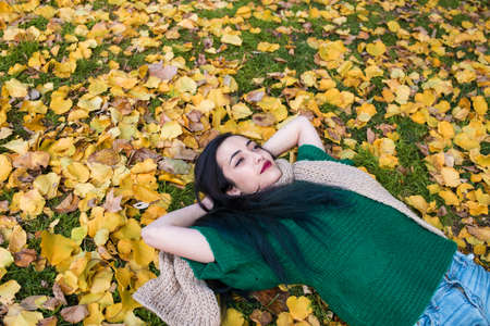 blue hair: Woman with red lips and blue hair lying on autumnal foliage in park.
