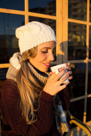 to get warm: Portrait of young woman drinking coffee.