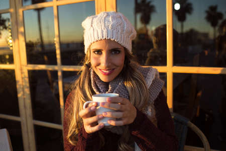 to get warm: Portrait of young woman drinking coffee and looking at camera. Close-up. Outdoors