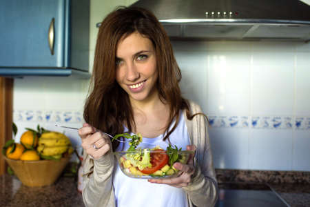 green eyes: Portrait of young woman with green eyes eating salad.