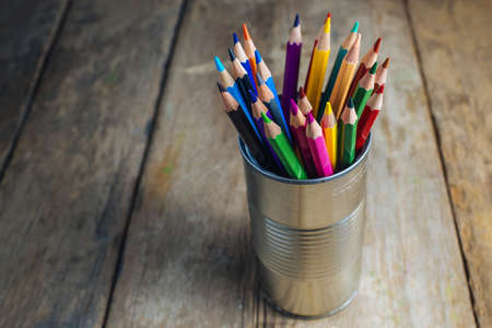 Colored pencils stuck in a can on old wood. Stock Photo