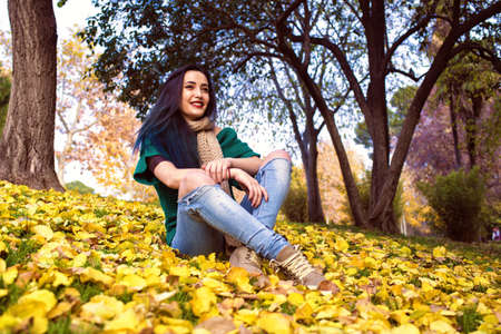 having fun in winter time: Young woman with blue hair sitting in park in autumn