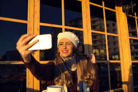 wink: Young woman making selfie on her phone and wink out while sitting in cafe outdoors