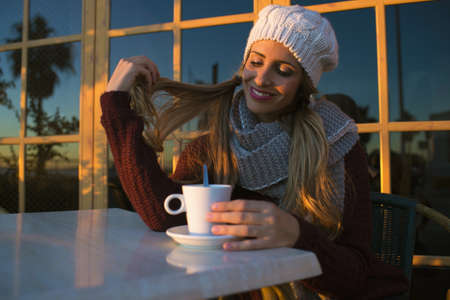 to get warm: Portrait of young woman with coffee sitting in coffee shop. Stock Photo